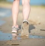 Sport footwear, sand footprints and legs close up Royalty Free Stock Photos