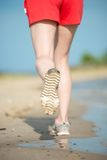 Sport footwear, sand footprints and legs close up Stock Photography