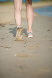 Sport footwear, sand footprints and legs close up Stock Photos