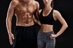 Sport, forma fisica, concetto di allenamento Coppie adatte, forte uomo muscolare e donna esile posanti su un fondo nero Immagine Stock