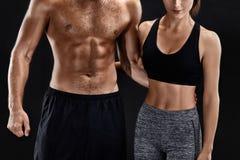 Sport, forma fisica, concetto di allenamento Coppie adatte, forte uomo muscolare e donna esile posanti su un fondo nero Fotografia Stock