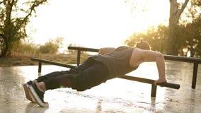 Sport, forma fisica, giovane uomo muscolare che risolve durante l'allenamento sulla via L'atleta che caucasico fare spinge aument archivi video