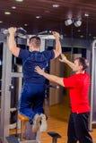 Sport, forma fisica, lavoro di squadra, concetto della gente di culturismo - uomo ed istruttore personale con il gruppo di sollev Immagine Stock