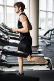 Sport, forme physique, mode de vie, technologie et concept de personnes - homme de sourire s'exerçant sur le tapis roulant dans l Photo stock