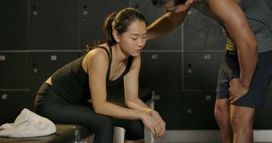 Sport-Frau geben bis zur Übung und zu ihrem persönlichen Trainer, die sie Übung zu tun fortzufahren aufmunternd sind, und angespo stock footage