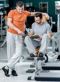 Sport friendship. Two young smiling athlete sit among trainers i Stock Photo