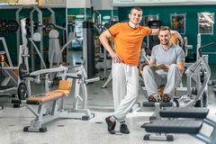 Sport friendship. Two young smiling athlete sit among trainers i Royalty Free Stock Photo