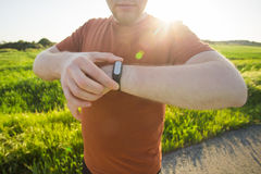 Sport, gadget, activity tracker and people concept - Close up of runner jogging outside looking at his wearable fitness stock image