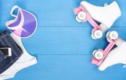 Sport, gesunder Lebensstil, Rollschuhlaufenhintergrund Weiße Rollschuhe, Kleidungssatz, Handy und rosa Maskenhut Flache Lage, t stockbild