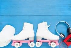 Sport, gesunder Lebensstil, Rollschuhlaufenhintergrund Weiße Rollschuhe, Kopfhörer und weiße Baseballmütze Flache Lage, Draufsich stockbild