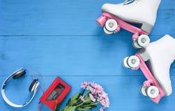 Sport, gesunder Lebensstil, Rollschuhlaufenhintergrund Weiße Rollschuhe, Kopfhörer und WeinleseKassettenrekorder Flache Lage lizenzfreies stockbild