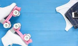 Sport, gesunder Lebensstil, Rollschuhlaufenhintergrund Weiße Rollschuhe, Mädchenkleidungssatz, Handy Flache Lage, Draufsicht stockfotografie