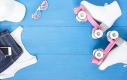 Sport, gesunder Lebensstil, Rollschuhlaufenhintergrund Weiße Rollschuhe, Mädchenkleidungssatz, Handy, Sonnenbrille und weiße Basi lizenzfreie stockbilder