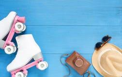 Sport, gesunder Lebensstil, Rollschuhlaufenhintergrund Weiße Rollschuhe, Retro- Kamera, Strohhut und Retro- Sonnenbrille Flache L stockfoto