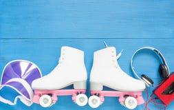 Sport, gesunder Lebensstil, Rollschuhlaufenhintergrund Weiße Rollschuhe, Retro- Kopfhörer und rosa Maskenhut Flache Lage, Draufsi stockfoto