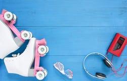 Sport, gesunder Lebensstil, Rollschuhlaufenhintergrund Weiße Rollschuhe, Sonnenbrille, headpfones und WeinleseKassettenrekorder F lizenzfreies stockbild