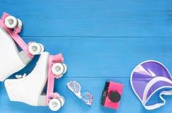 Sport, gesunder Lebensstil, Rollschuhlaufenhintergrund Weiße Rollschuhe, Sonnenbrille, rosa Maskenhut und Weinlesekamera Flache L lizenzfreie stockfotografie