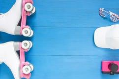 Sport, gesunder Lebensstil, Rollschuhlaufenhintergrund Weiße Rollschuhe, Sonnenbrille, weiße baceball Kappe, rosa Kamera der Wein lizenzfreies stockbild