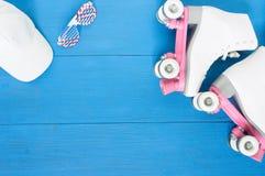 Sport, gesunder Lebensstil, Rollschuhlaufenhintergrund Weiße Rollschuhe, Sonnenbrille, weiße Baseballmütze Flache Lage, Spitze stockfotografie