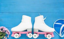Sport, gesunder Lebensstil, Rollschuhlaufenhintergrund Weiße Rollschuhe und blauer Maskenhut Flache Lage, Draufsicht stockbild