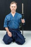 Sport giapponese di addestramento maschio caucasico, iaido Sedendosi sul pavimento che tiene una spada giapponese che esamina mac Fotografie Stock