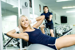 Sport girl. Happy cutie athletic girl ,  execute exercise on muscles belly  and smile, in  sport-hall Stock Images