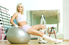 Sport girl. Happy cutie athletic girl ,  sit  on fitnes balls and smile, in  sport-hall Royalty Free Stock Photography