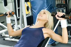 Sport girl. Happy cutie athletic girl ,  execute exercise  with dumbbells and smile, in  sport-hall Stock Photography