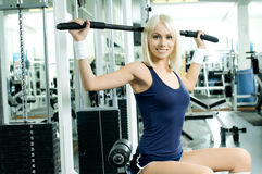Sport girl. Happy cutie athletic girl ,  execute exercise on sport-apparatus  and smile, in  sport-hall Royalty Free Stock Image