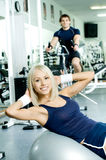 Sport girl. Happy cutie athletic girl ,  execute exercise on muscles belly  and smile, in  sport-hall Stock Image