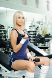 Sport girl. Happy cutie athletic girl ,  exercise with dumbbells and smile, in  sport-hall Royalty Free Stock Photos