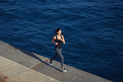 Sport girl in action running over ocean waves background. Full length portrait of cute young woman out jogging along the coastline at sunny day, dynamic picture royalty free stock photo