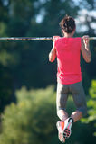 Sport girl athlete is Chin-ups and Pullups training on an abandoned sports field. Pull-up on the bar. Athlete Outdoors. stock images