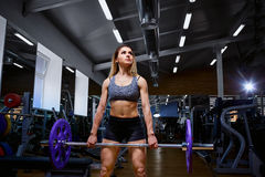 Sport girl with a barbell in her arms in the gym.  stock image
