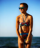 Sport girl in bikini on the beach near the sea, sunset time, golden hour light Royalty Free Stock Image