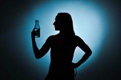 Sport girl drinking water, silhouette studio shot Royalty Free Stock Image