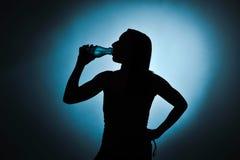 Sport girl drinking water, silhouette studio shot stock images