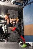 Sport girl is engaged in exercises TRX Stock Photos
