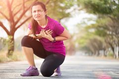 Sport girl have chest pain after jogging or running work out in park. Sport and Health care concept royalty free stock photo