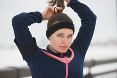 Sport girl have work out fitness at snow winter promenade - straightens hair, close up Royalty Free Stock Photo