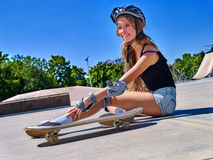 Sport girl with injury near her skateboard outdoor. Royalty Free Stock Image