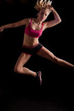 Sport girl jumping black background stock photography