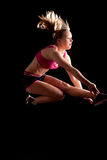 Sport girl jumping profile black background. Sporty blond young girl with pink top and shorts jumping high in profile on a black background royalty free stock photos