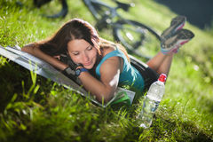 Sport girl lay on a grass with a map near the bicycle. Beautifu sport girl lay on a grass with a map near the bicycle Stock Photos