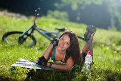 Sport girl lay on a grass with a map near the bicycle Stock Image