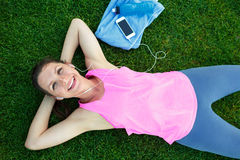 Sport girl lying on green grass after exercise Royalty Free Stock Photography