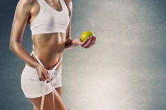 Sport girl with measure tape and green apple Stock Image