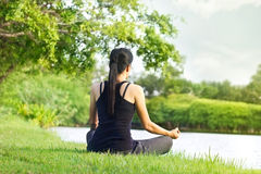 Sport girl meditating in nature green park at the sunrise Stock Photo