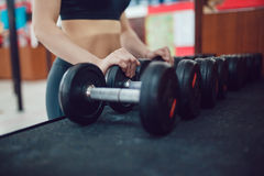 Sport girl is preparing for the exercise with dumbbells Royalty Free Stock Images