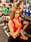Sport girl in red holding dumbbells at sport gym. Biceps into foreground. Stock Photo
